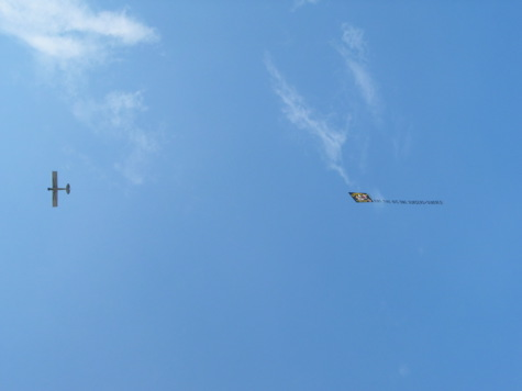 [picture: a plane flies overhead with a banner]
